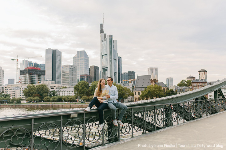 Posing on the Eiserner Steg bridge in front of the 'Mainhattan' skyline of Frankfurt am Main | Photo by Irene Fiedler for Tourist is a Dirty Word Blog