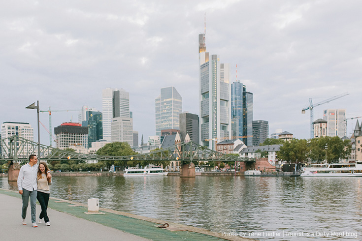 Strolling along the Main riverfront with the Eiserner Steg bridge and 'Mainhattan' skyline of Frankfurt am Main in the background | Photo by Irene Fiedler for Tourist is a Dirty Word Blog