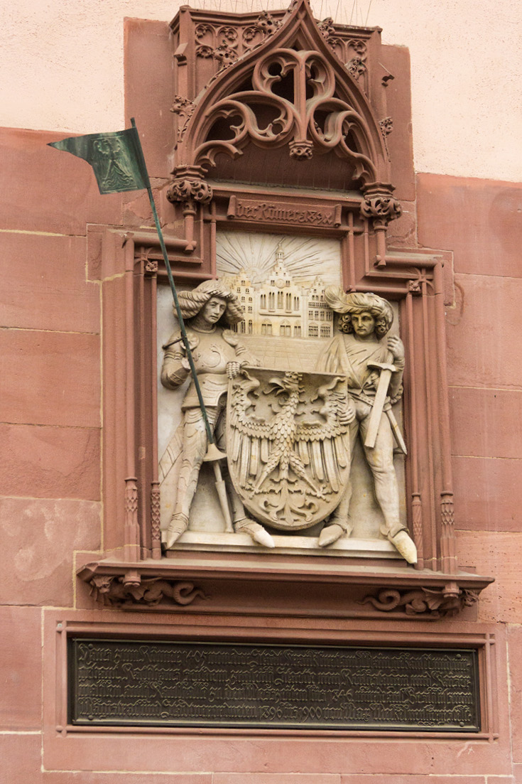 "Wall relief commemorates the 1900 remodel, ""House of the Romans, bought and rebuilt by the city of Frankfurt am Main in 1405, and the town hall of Reichstag and Imperial elections 1886 to 1900 by Max Meckel, newly manufactured."""