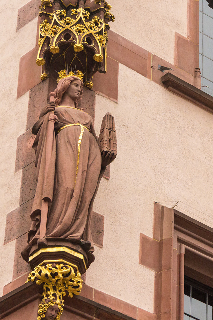 On the neighboring building front to the left of the Roemer, the Alt-Limburg house, be sure to see the 'Frankfurtia', Statue, or as Germans know her, Francofurtia, the female embodiment, protector of the city of Frankfurt. She's holding the sword of Charlemagne in her right hand and the Pfarrturm, church tower in her left.