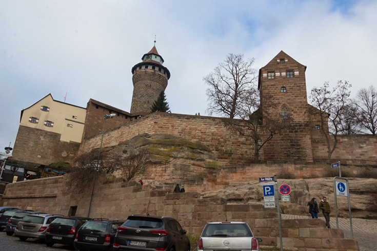 The Imperial Castle of Nuremberg sitting on its hill with the odd juxtaposition of a modern parking lot in front of a medieval castle
