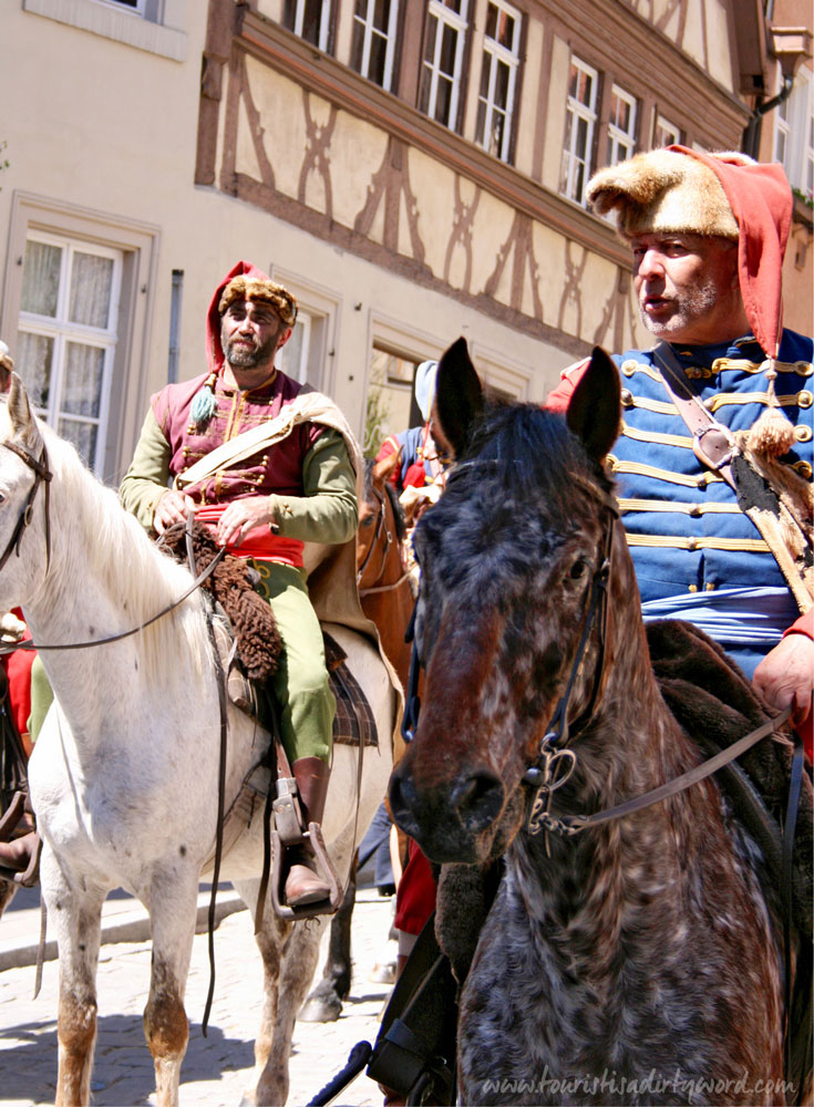 Historically costumed riders parade through the streets of Rothenburg during The Master Draught festival