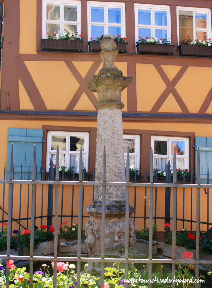 Little garden and statue in front of a half-timbered house in Rothenburg ob der Tauber