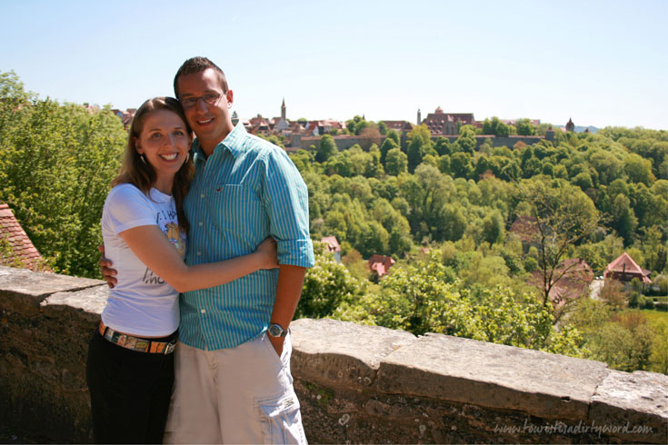Denise and Sebastian, bloggers of Tourist is a Dirty Word, a Germany Travel Blog, on the town wall of Rothenburg ob der Tauber